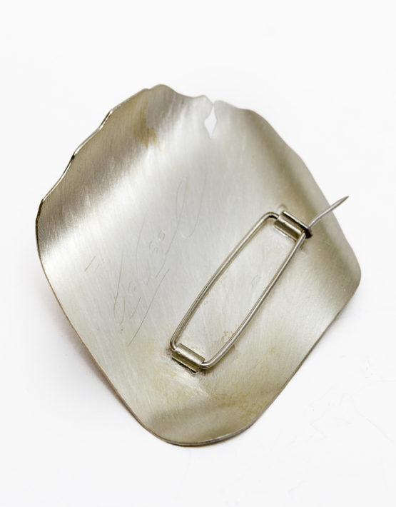 Parte trasera de un prendedor de plata con forma de pétalo
